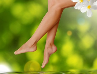 Long woman legs  on green background. Spa concept