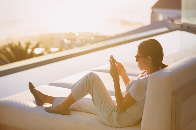 Jeune femme qui utilise son smartphone sur sa terrasse