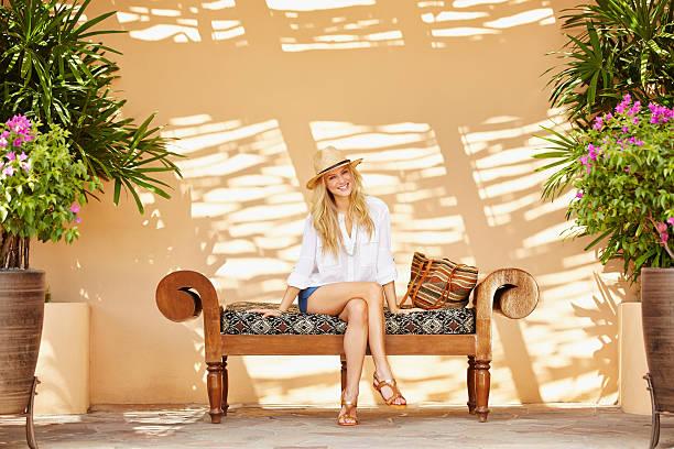 Jeune femme assise sur un banc à l'ombre sur sa terrasse