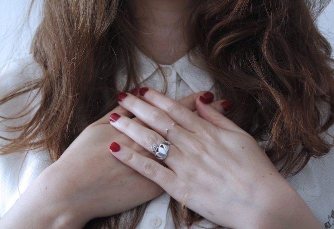 Femme mains croisées bague argent