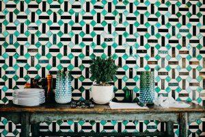 Vases et assiettes sur un meuble en bois devant un mur en mosaique verte, blanche et noire