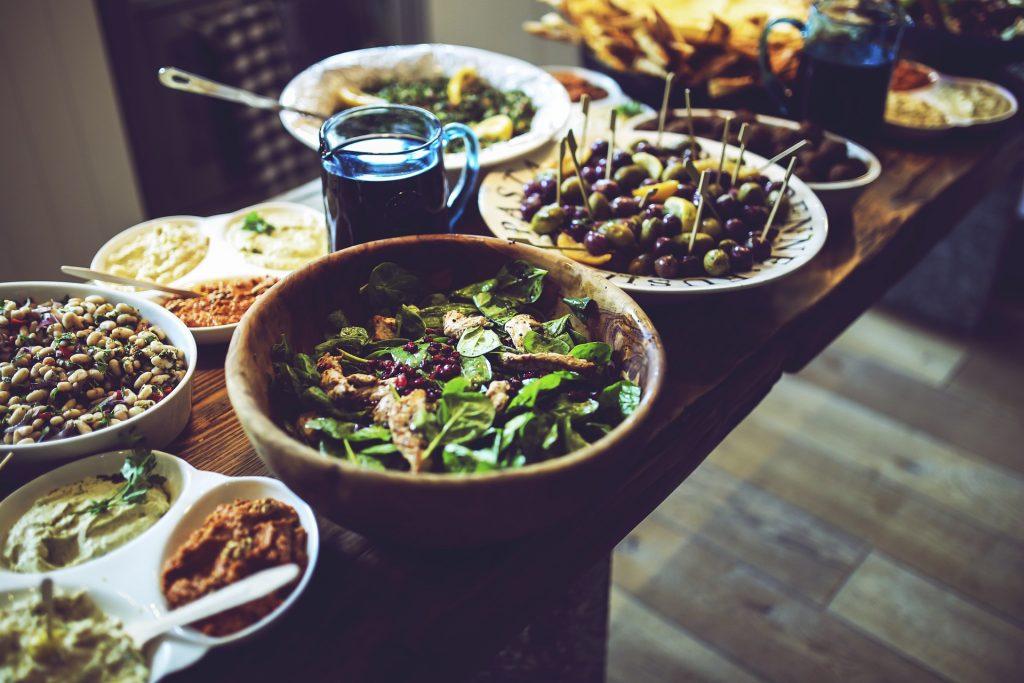 Buffet de plusieurs spécialités apéritives disposées dans des plats sur une table en bois