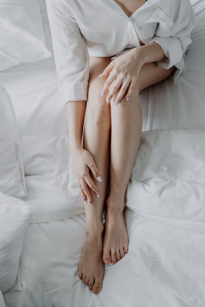 femme qui met de la crême sur ses jambes
